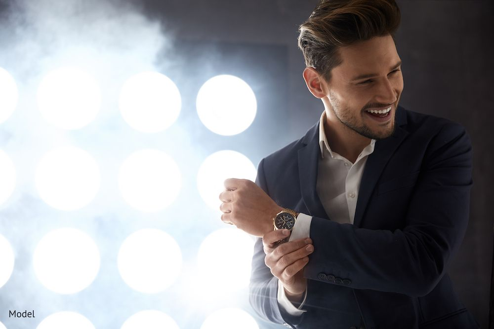 Attractive man in suit with white teeth in front of lights