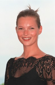 Model Kate Moss smiling in black lace dress and sleek updo