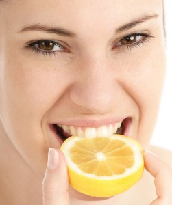 Young woman with nice teeth biting into a lemon