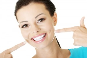 A smiling woman pointing to her perfect teeth on a white background