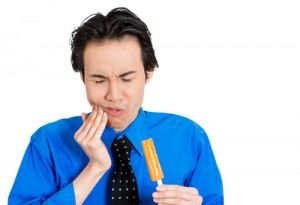 Portrait of a man putting his hand to his cheek from pain from frozen popsicle in his hand, isolated white background