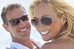 man and woman smiling with white smiles wearing sunglasses