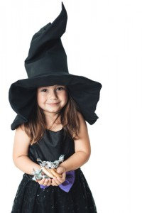 little girl witch costume holding Halloween candy
