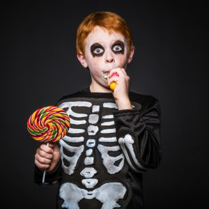 boy dressed in skeleton costume eating Halloween candy