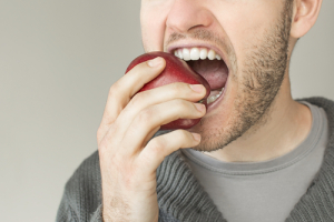 Close up of a man biting into an apple