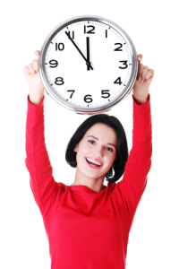 Happy young woman holding a large clock over her head