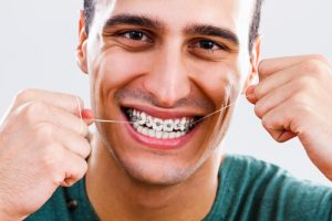 Man flossing with braces on