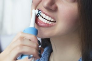 Close up of brushing teeth with electric toothbrush
