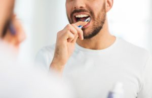 close up of young man with toothbrush cleaning teeth and looking to mirror at home bathroom