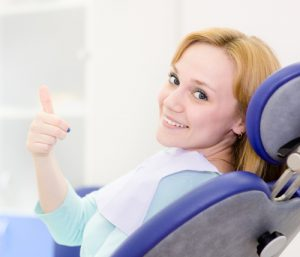 Woman in dentist chair with thumbs up