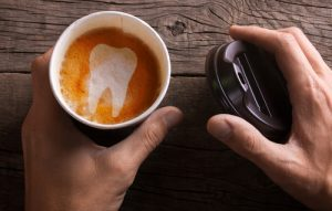 Paper cup of coffee is held by a man in his hand. Coffee makes teeth yellow and sick-img-blog