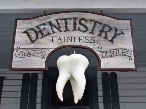 Vintage sign with giant tooth hanging in front of dentist office-img-blog