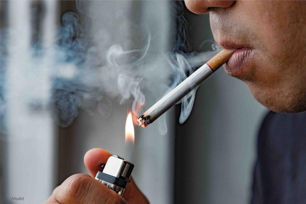 Young man smoking a cigarette.