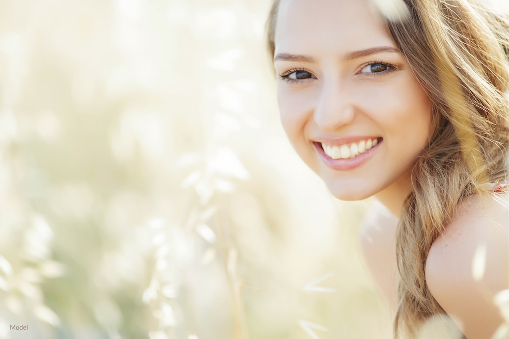 Woman smiling with straight teeth that is possible with Invisalign®.