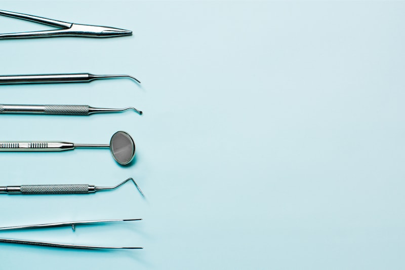 Dentist tools on light blue background: corncang, curette, dental probe, gross-mayer clamp, dental mirror and explorer.