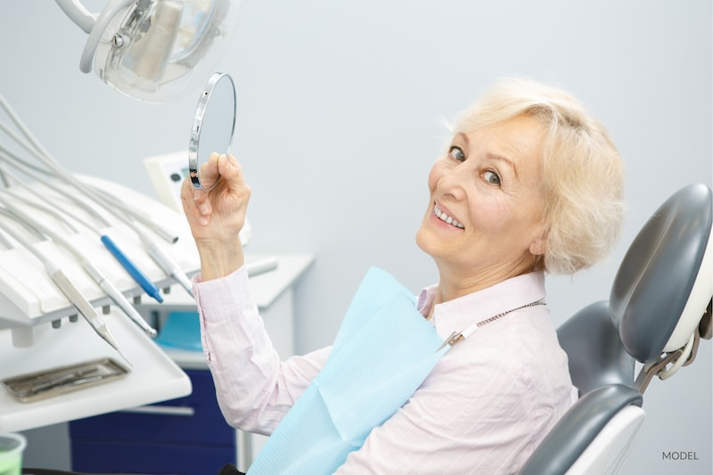 Older woman smiling in dental chair after looking at her new smile in the mirror.