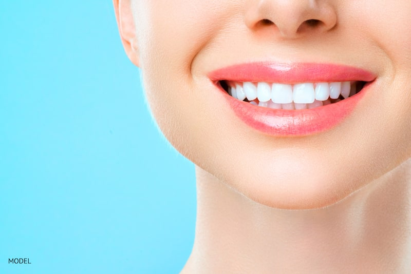woman smiling with white teeth behind a blue background.