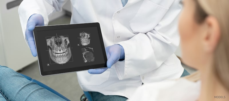 Dental patient sitting in the chair looking at x-rays of her dental structure.