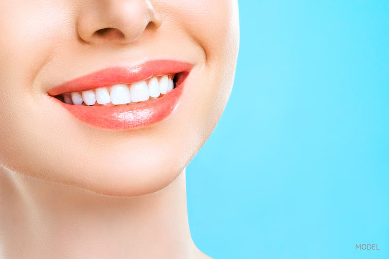 Young woman with healthy, white teeth smiling in front of a blue background.