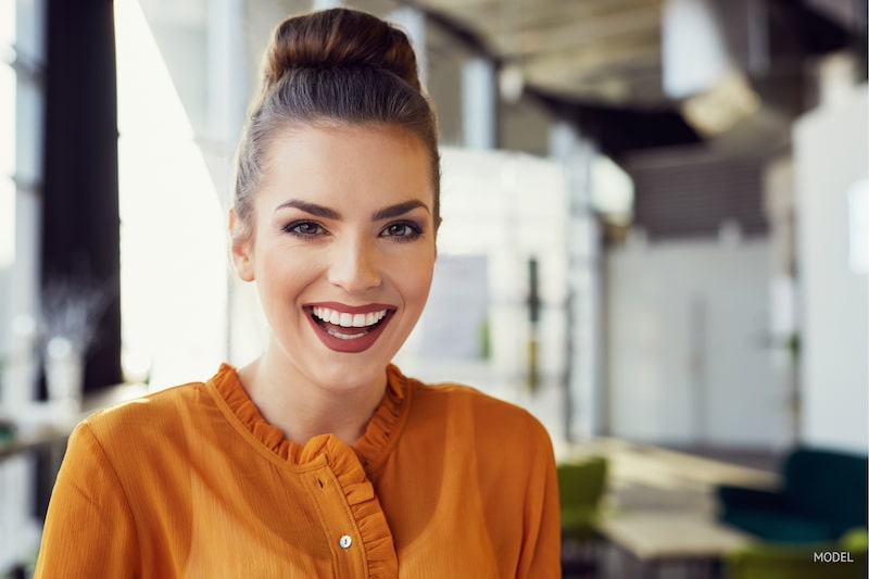 Woman with her hair in a bun, showing off her big, beautiful smile.